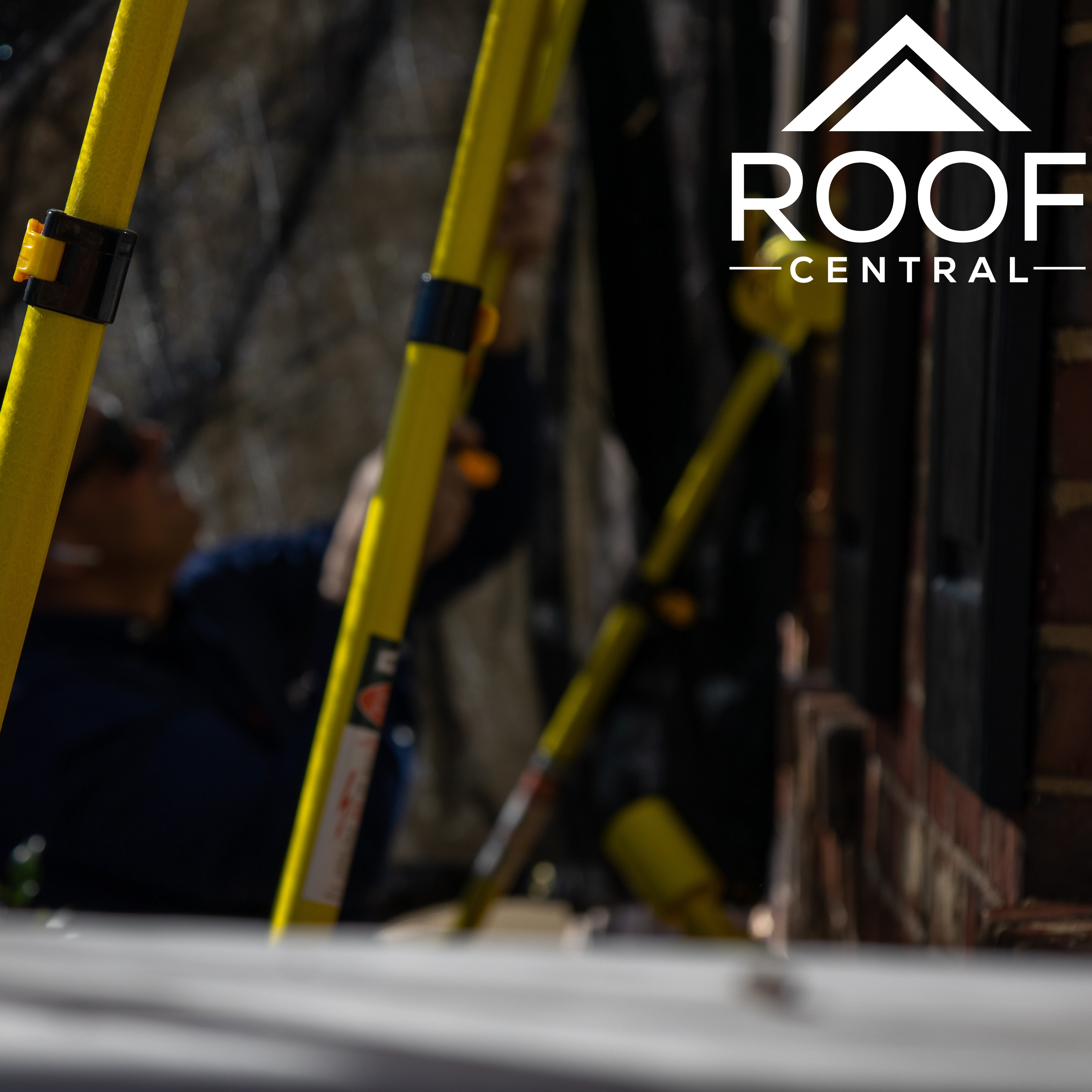 A roofer working on security safety equipment in front of a house.