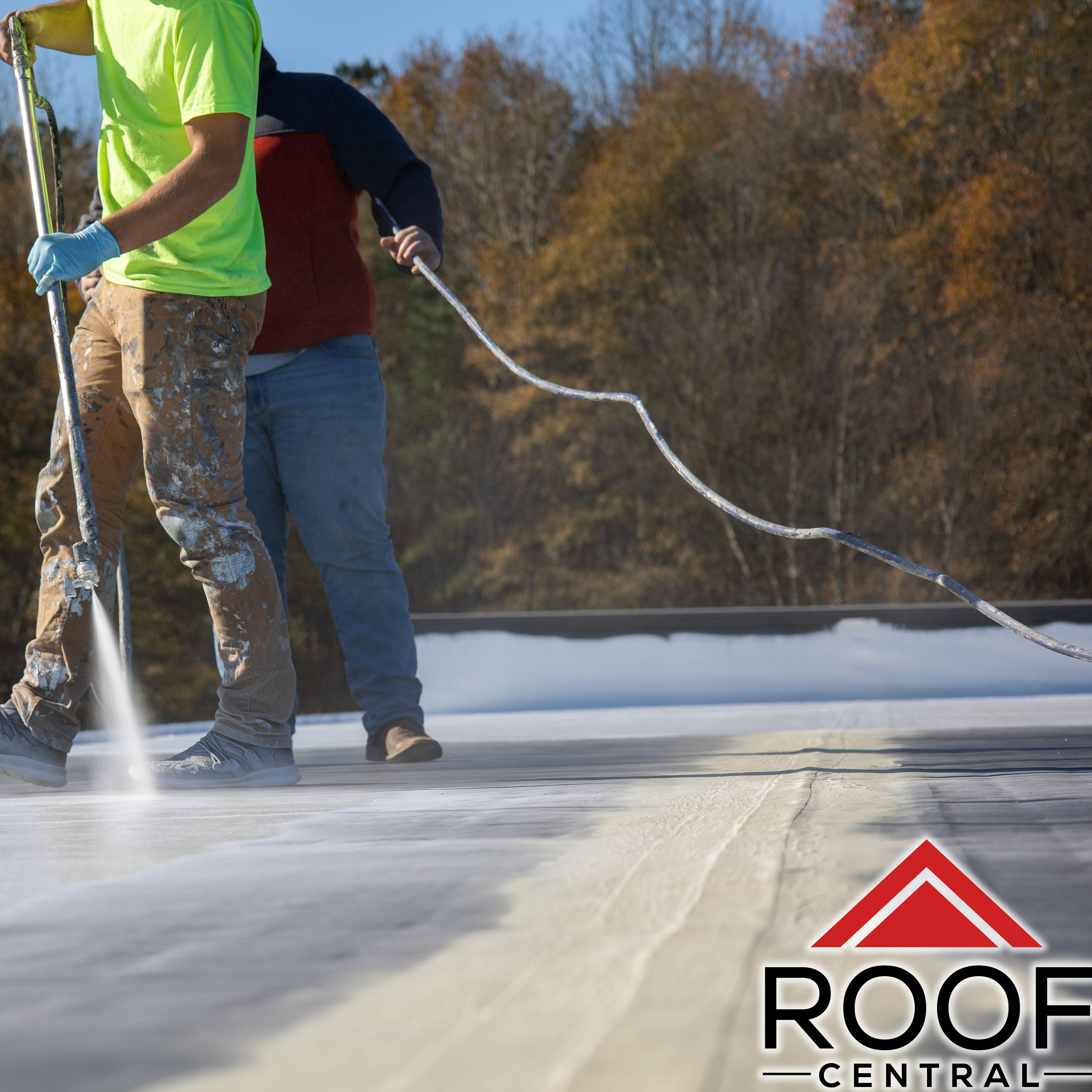 Workers finishing up a top layer of a commercial roof coating.