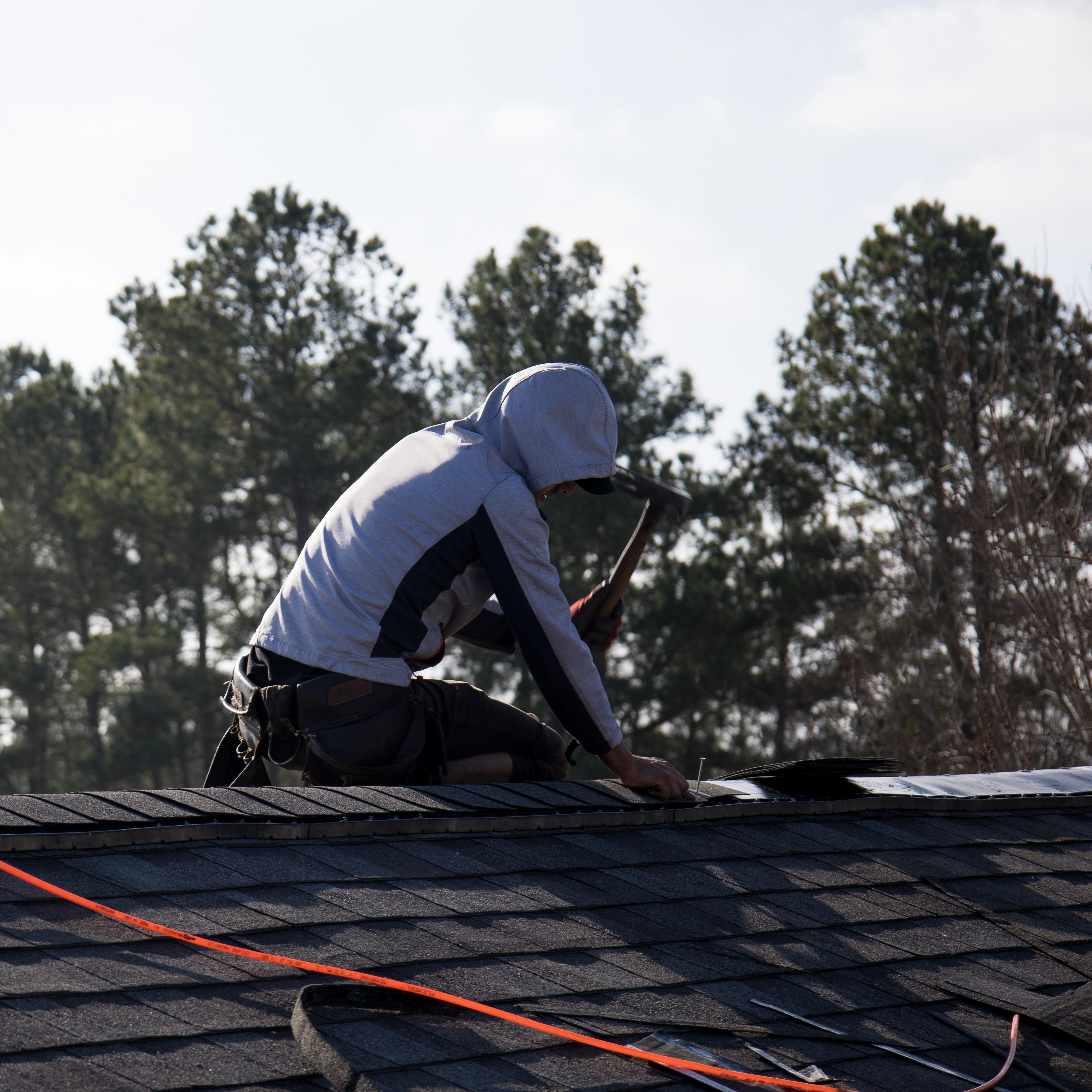 A roofer nailing shingles by hand on a roof.