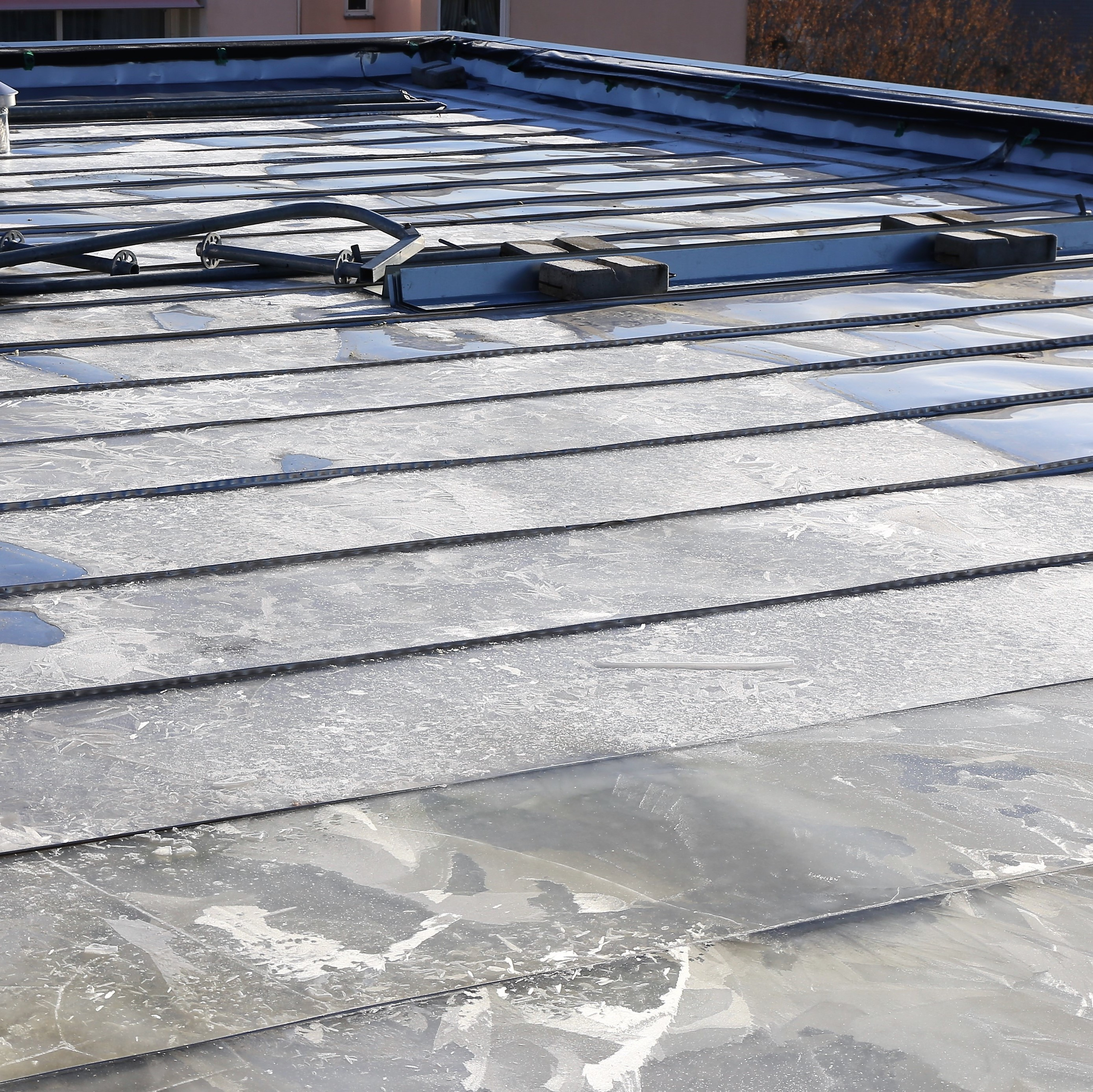 A metal roof that is has ice on it.