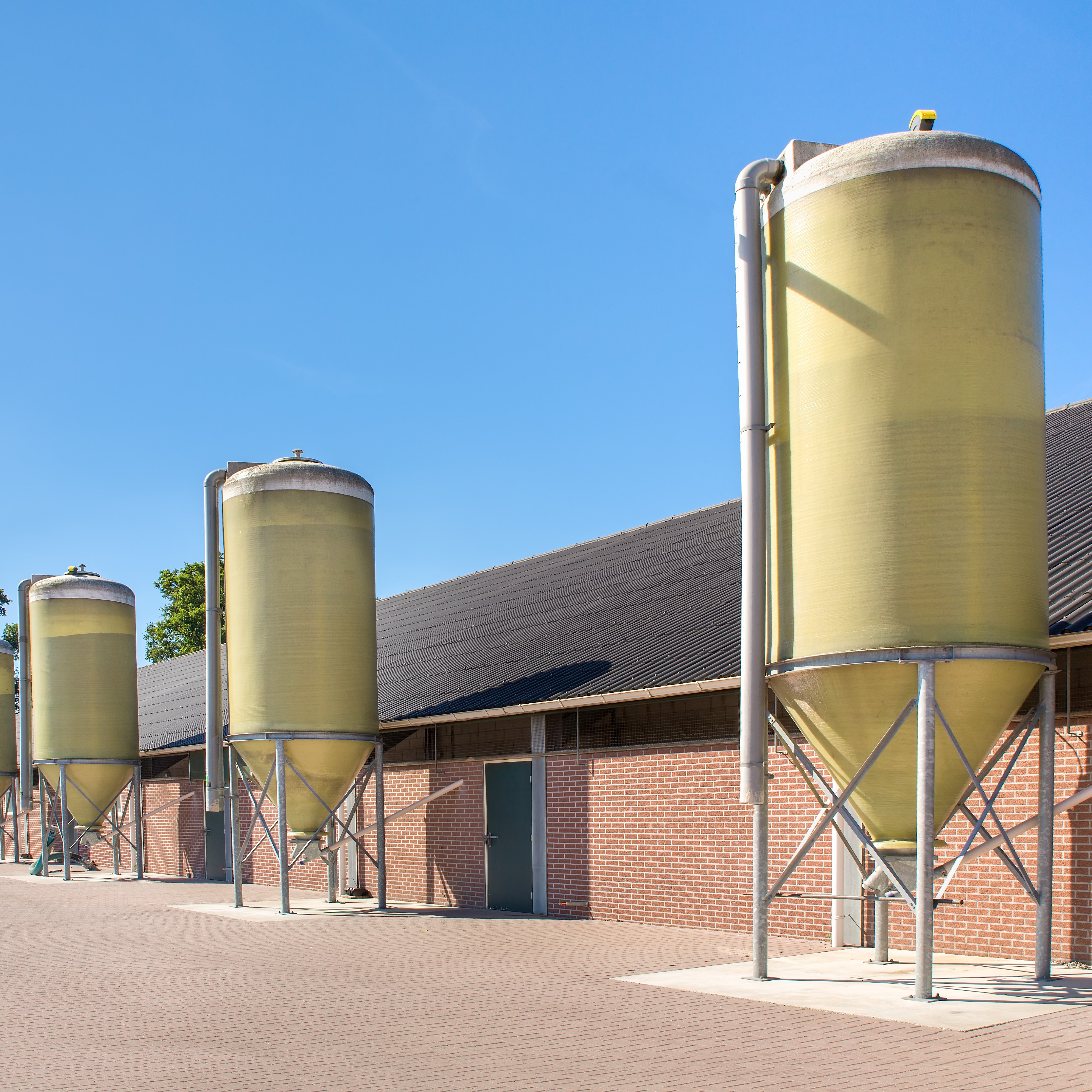 The side of an agricultural building with metal silos present as well.
