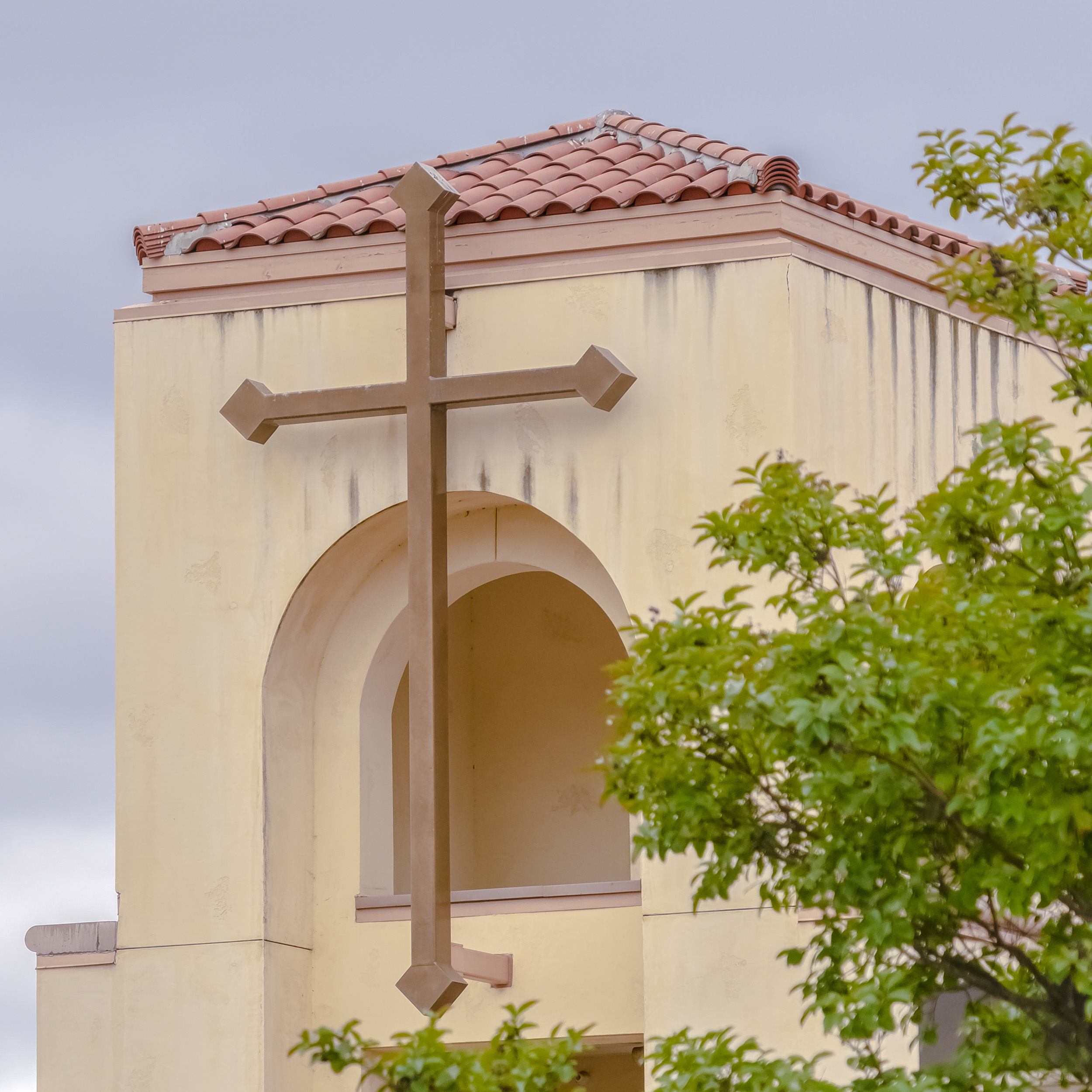 Part of a church building with tile roofing and a large cross.