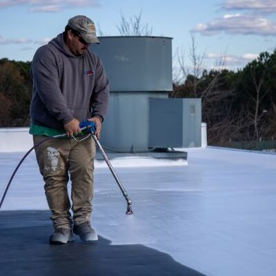 A Contractor Sprays Flat Roof Coating.