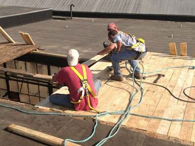 Roofing Contractors Work on Commercial Roofs.